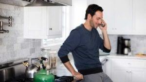 Man on phone in kitchen