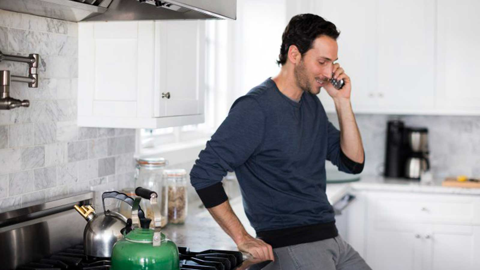Man on phone in kitchen
