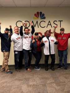 red sox fans in front of the Comcast sign