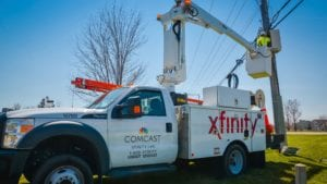 An Xfinity truck extends its crane to reach machinery on a telephone pole.
