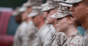Members of the armed forces stand next to each other in a line.