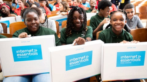 Students receive Internet Essentials laptops at an event in Boston.